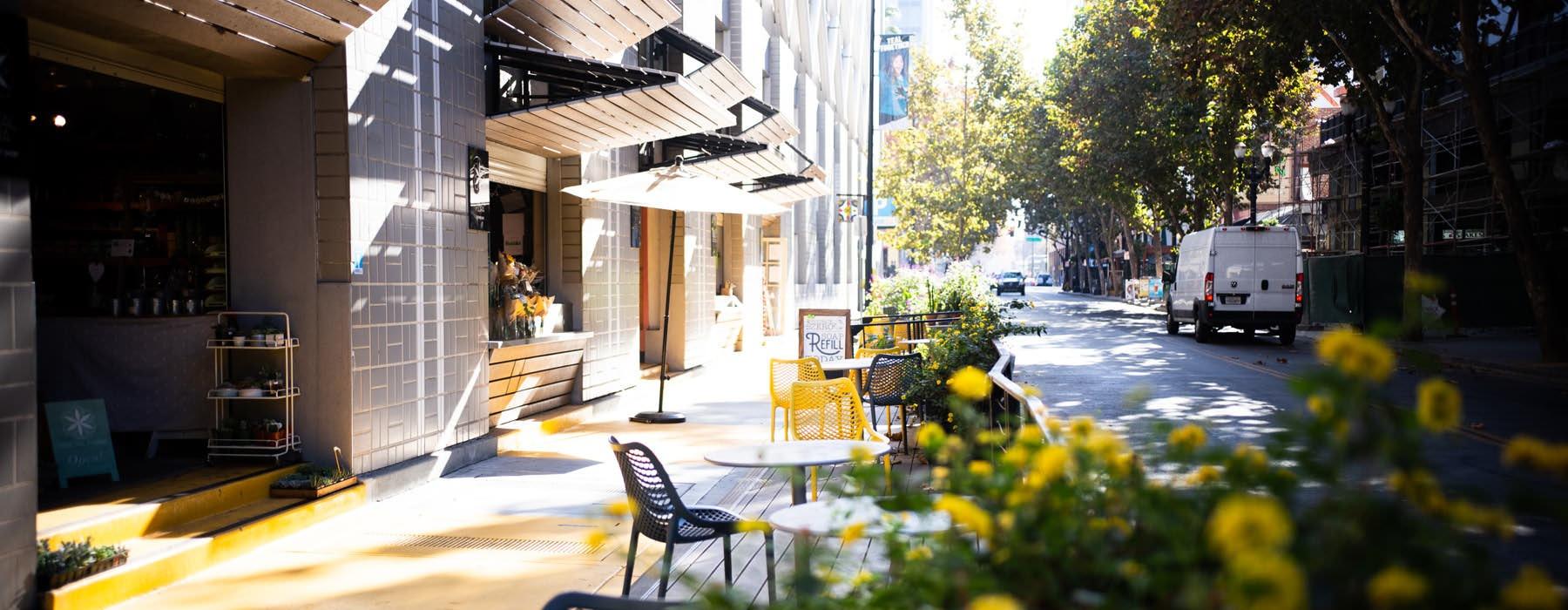 dining tables on sidewalk, in front of neighborhood restaurant